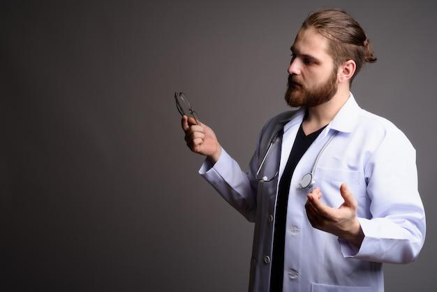 Jovem médico barbudo contra uma parede cinza