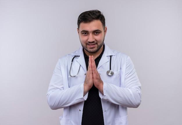 Jovem médico barbudo vestindo jaleco branco com estetoscópio de mãos dadas em gesto de oração, sentindo-se grato e feliz
