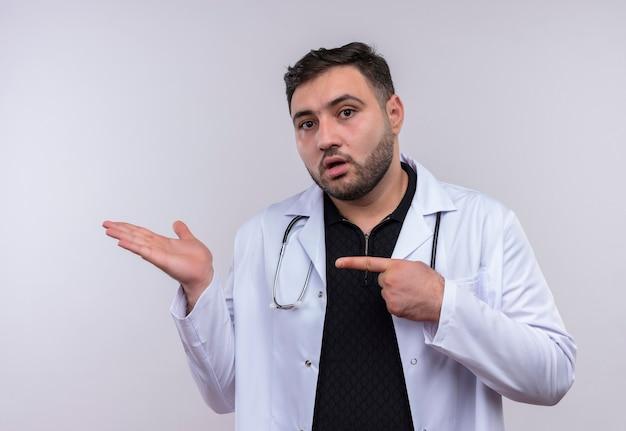 Jovem médico barbudo vestindo jaleco branco com estetoscópio mostrando o braço e a mão apontando com o dedo indicador para o braço
