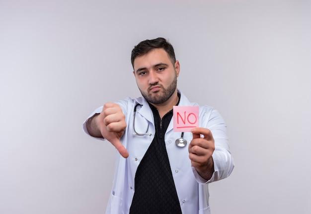Jovem médico barbudo vestindo jaleco branco com estetoscópio segurando um papel remonder com a palavra não parece descontente e mostra antipatia