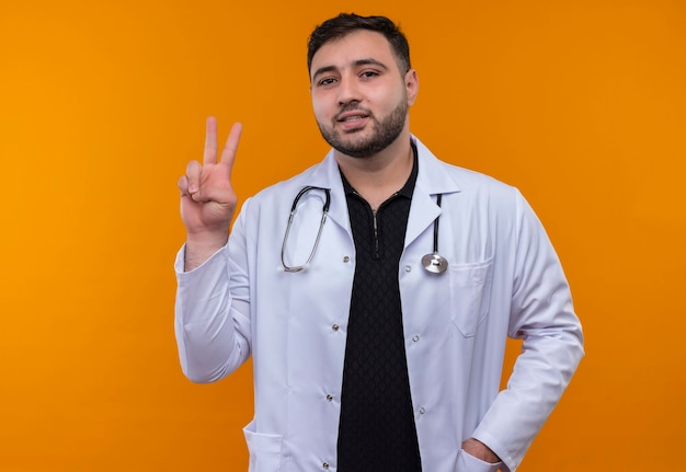 Jovem médico barbudo vestindo jaleco branco com estetoscópio sorrindo mostrando o número dois ou sinal de vitória