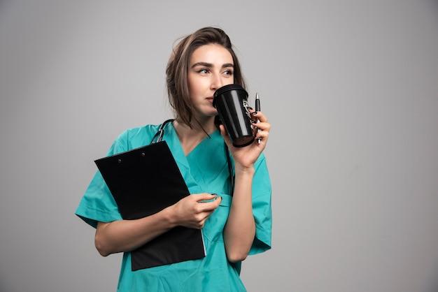 Jovem médico bebendo café na parede cinza.