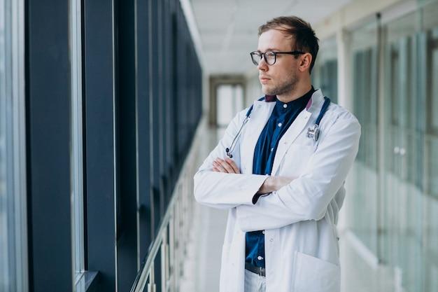 Jovem médico bonitão com estetoscópio na clínica