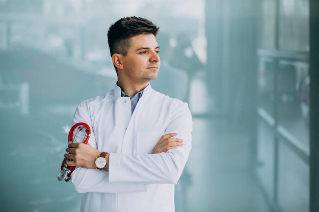 Jovem médico bonito em uma túnica médica com estetoscópio