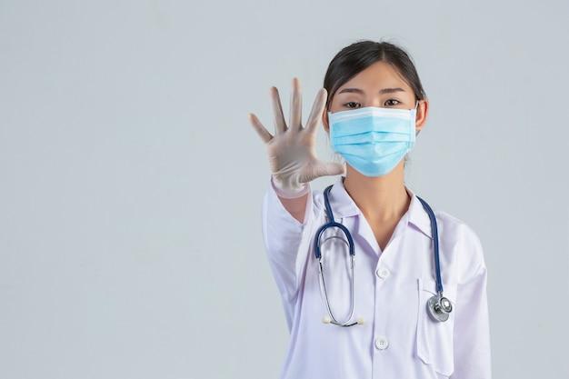 Jovem médico bonito está usando máscara ao fazer parar a mão na parede branca.