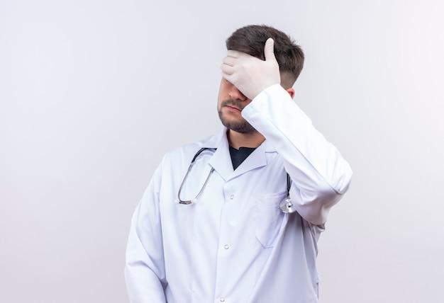 Jovem médico bonito usando jaleco branco com luvas médicas e estetoscópio chateado fazendo face com a palma da mão em pé sobre a parede branca