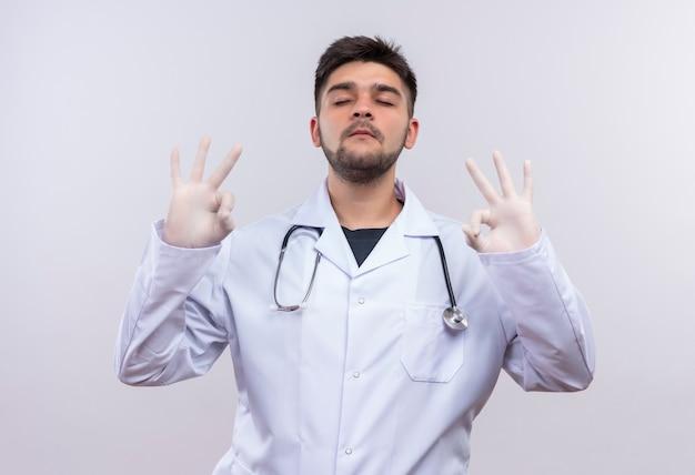 Jovem médico bonito usando jaleco branco, luvas médicas brancas e estetoscópio tentando se acalmar, mostrando sinal de ok com as mãos fechando os olhos em pé sobre a parede branca