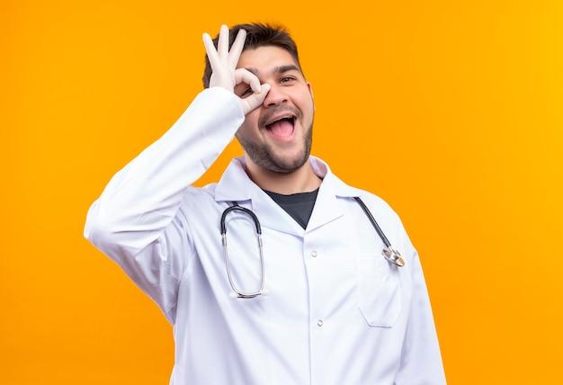 Jovem médico bonito usando jaleco branco, luvas médicas e estetoscópio, fazendo sinal de ok no olho com a mão em pé sobre a parede laranja