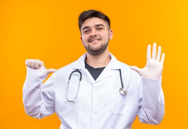 Jovem médico bonito usando jaleco branco, luvas médicas e estetoscópio mostrando seis horas com as mãos em pé sobre a parede laranja