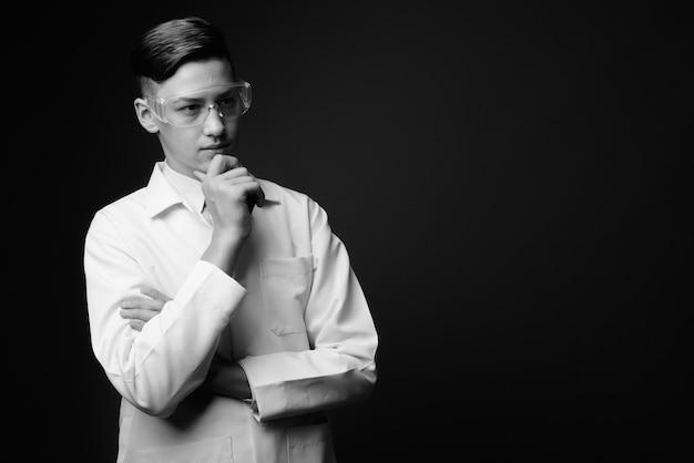 - jovem médico bonito usando óculos de proteção em preto e branco