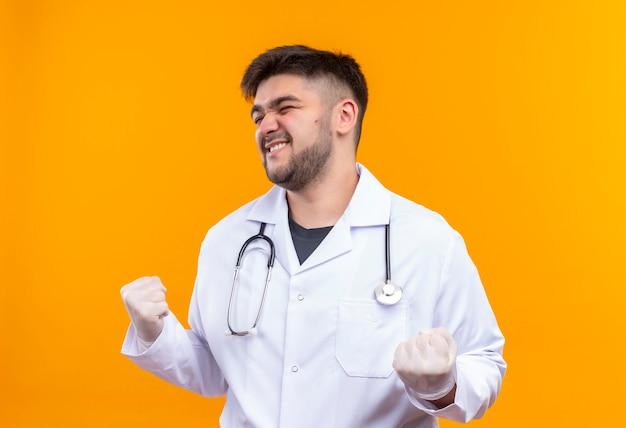 Jovem médico bonito usando um avental médico branco, luvas médicas brancas e estetoscópio, olhando feliz para os resultados