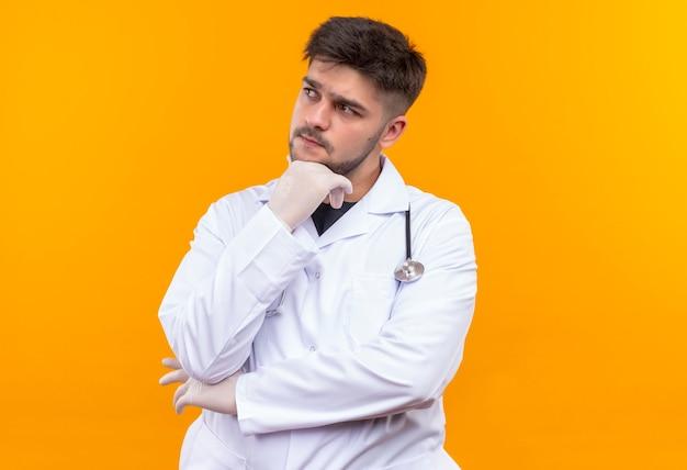 Jovem médico bonito usando um avental médico branco, luvas médicas brancas e estetoscópio, olhando pensativamente para além de uma parede laranja