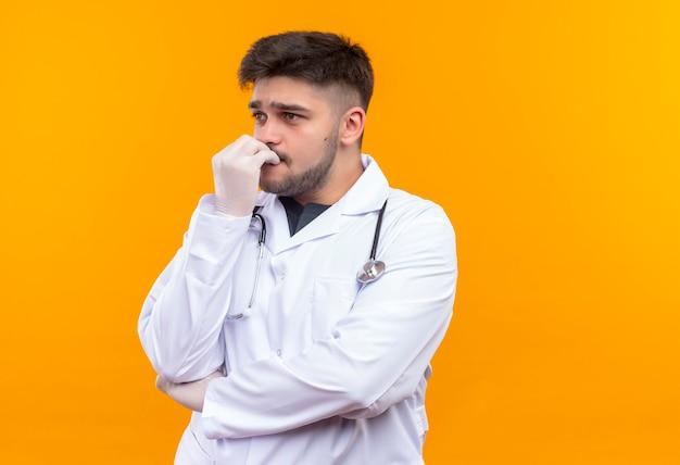 Jovem médico bonito usando um avental médico branco, luvas médicas brancas e estetoscópio, parecendo assustado em pé sobre a parede laranja
