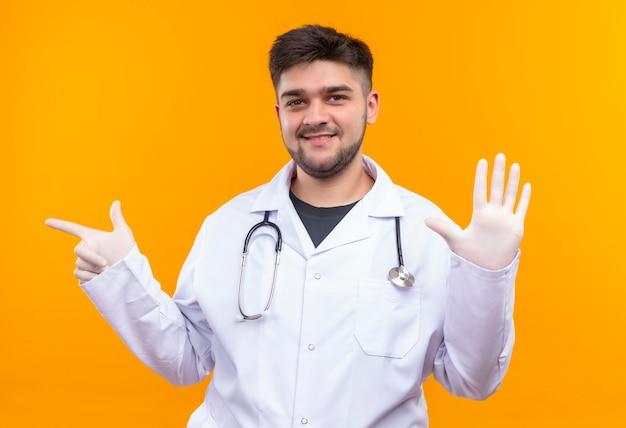 Jovem médico bonito vestindo jaleco branco com luvas médicas e estetoscópio sorrindo alegremente mostrando cinco sinais com os dedos e apontando para a direita em pé sobre a laranja