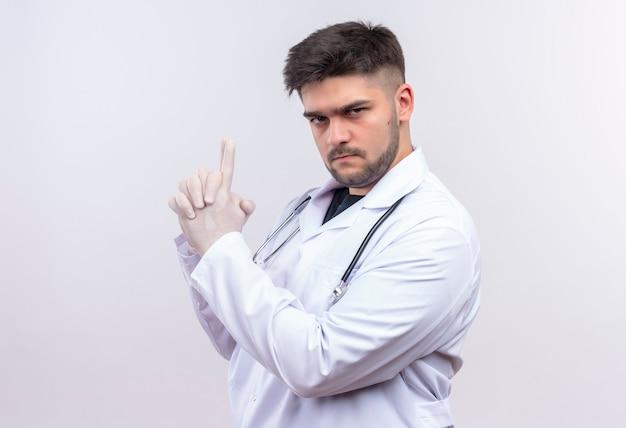 Jovem médico bonito vestindo jaleco branco, luvas médicas brancas e estetoscópio, olhando sério fazendo uma arma com as mãos em pé sobre a parede branca