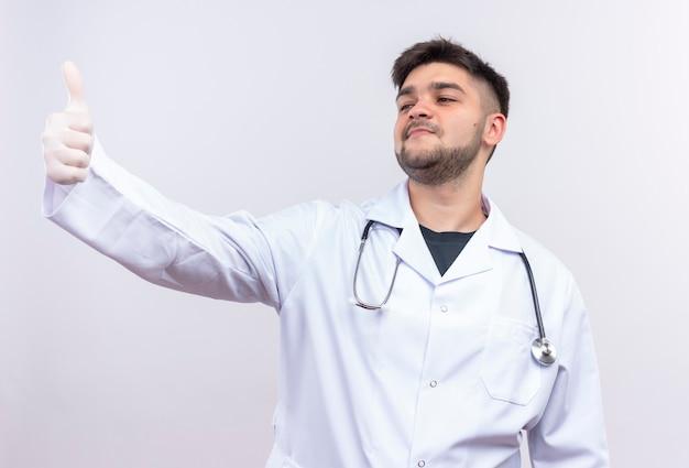 Jovem médico bonito vestindo jaleco branco, luvas médicas e estetoscópio fazendo um feliz polegar para cima, olhando além de pé sobre uma parede branca