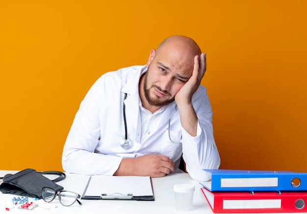 Jovem médico careca cansado, vestindo túnica médica e estetoscópio sentado na mesa de trabalho com ferramentas médicas, colocando a mão na bochecha em laranja