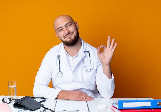 Jovem médico careca satisfeito usando roupão médico e estetoscópio sentado na mesa de trabalho