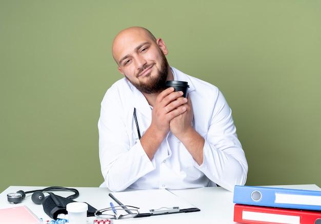 Jovem médico careca satisfeito, vestindo túnica médica e estetoscópio sentado na mesa, trabalhando com ferramentas médicas, segurando uma xícara de café isolada no fundo verde