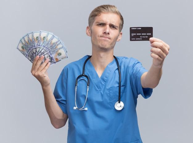 Jovem médico carrancudo vestindo uniforme de médico com estetoscópio segurando dinheiro e cartão de crédito para a câmera isolada na parede branca