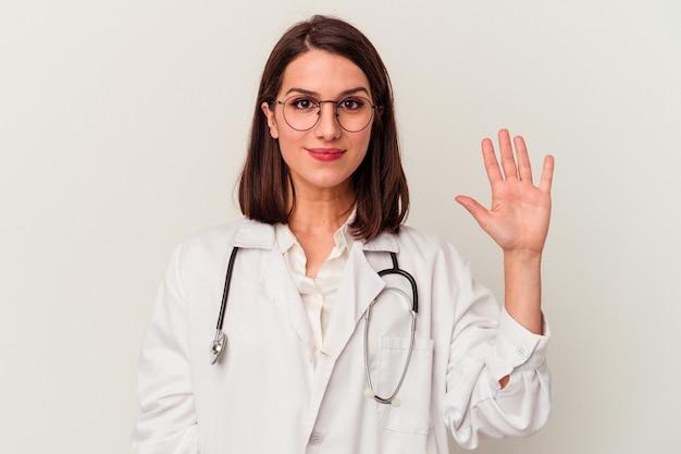 Jovem médico caucasiana, isolada no fundo branco, sorrindo alegre mostrando o número cinco com os dedos.