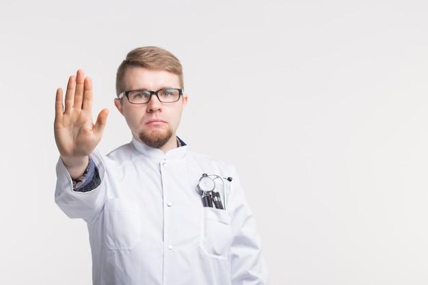 Jovem médico caucasiano com gesto de parada em branco com espaço de cópia
