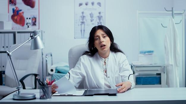 Jovem médico caucasiano na chamada de vídeo online, oferecendo suporte médico. médico usando tecnologia da internet para consultar pacientes durante a pandemia global covid-19. telemedicina e suporte de saúde.