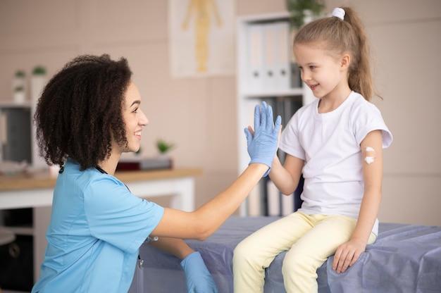 Jovem médico certificando-se de que a menina está bem após a vacinação