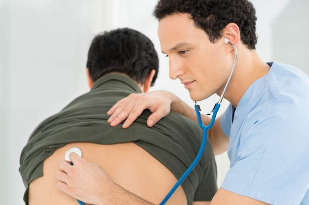 Jovem médico checando paciente com estetoscópio no hospital
