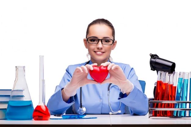 Jovem médico com coração vermelho isolado no branco
