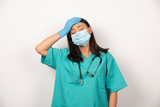 Jovem médico com dor de cabeça em fundo branco. foto de alta qualidade