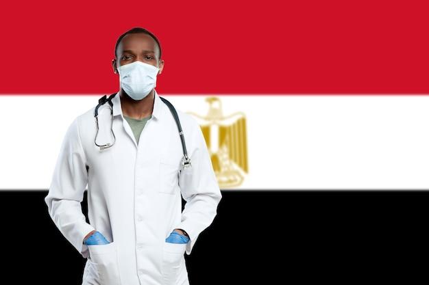 Jovem médico com estetoscópio e máscara facial, orando a deus com a bandeira nacional do egito no fundo