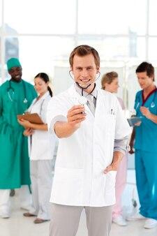 Jovem médico com estetoscópio e sua equipe