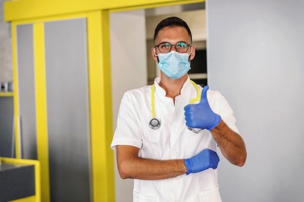 Jovem médico com luvas de borracha, máscara protetora e uniforme branco estéril em pé no hospital e mostrando os polegares.