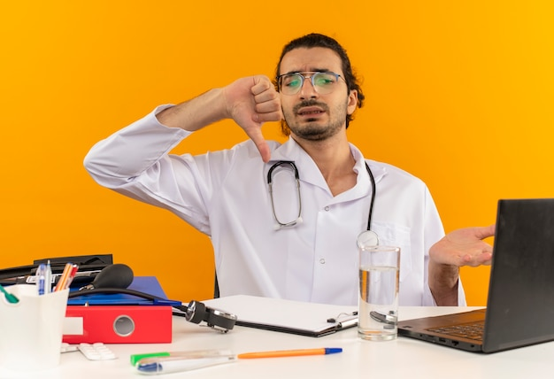Jovem médico confuso com óculos médicos, usando roupão médico e estetoscópio sentado na mesa