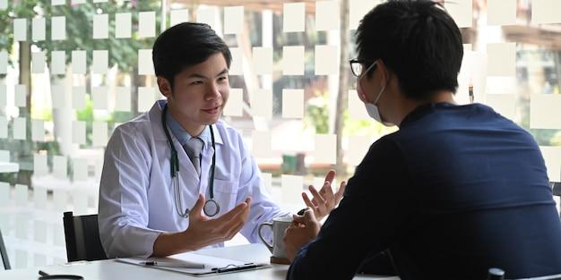 Jovem médico conversando / explicando ao paciente sobre vírus e pandemia enquanto sentados juntos na mesa de trabalho do médico sobre a clínica moderna