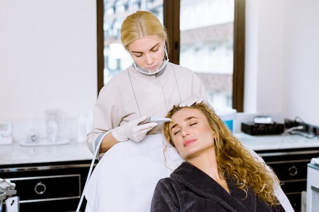 Jovem médico cosmetologista faz o procedimento de microdermoabrasão da pele facial de uma bela