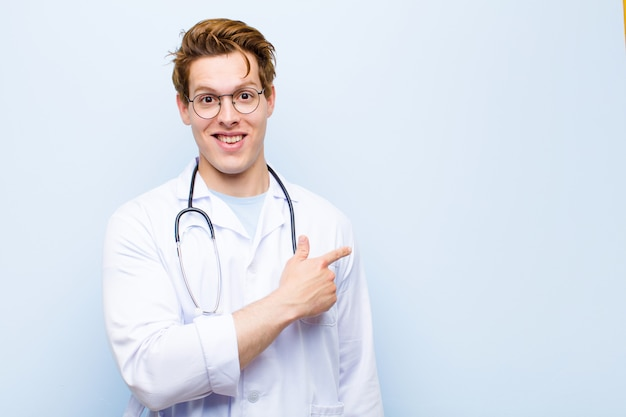 Jovem médico de cabeça vermelha, olhando animado e surpreso, apontando para o lado
