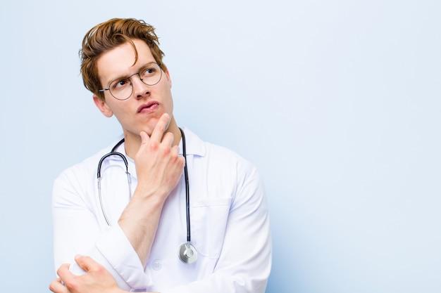 Jovem médico de cabeça vermelha pensando, se sentindo duvidoso e confuso, com opções diferentes, imaginando qual decisão tomar na parede azul