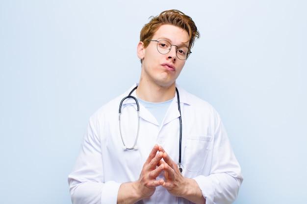 Jovem médico de cabeça vermelha planejando e conspirando, pensando em truques e trapaceiros desonestos, astúcia e traição contra a parede azul