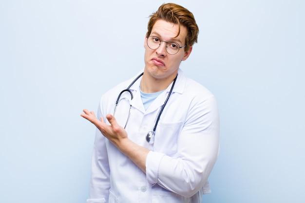 Jovem médico de cabeça vermelha se sentindo confuso e sem noção, pensando em uma explicação ou pensamento duvidoso contra a parede azul