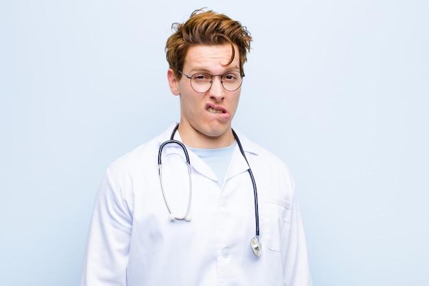 Jovem médico de cabeça vermelha se sentindo sem noção, confuso e incerto sobre qual opção escolher, tentando resolver o problema contra a parede azul