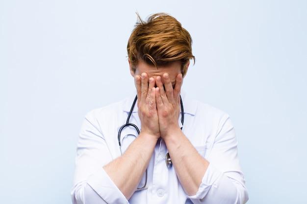 Jovem médico de cabeça vermelha, sentindo-se triste, frustrado, nervoso e deprimido, cobrindo o rosto com as duas mãos, chorando a parede azul
