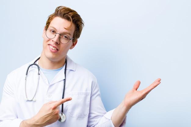 Jovem médico de cabeça vermelha sorrindo alegremente e apontando para copiar o espaço na palma da mão, mostrando ou anunciando um objeto contra a parede azul