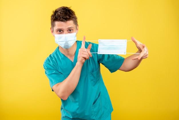 Jovem médico de frente para o sexo masculino com traje médico e máscara estéril segurando outra máscara no fundo amarelo