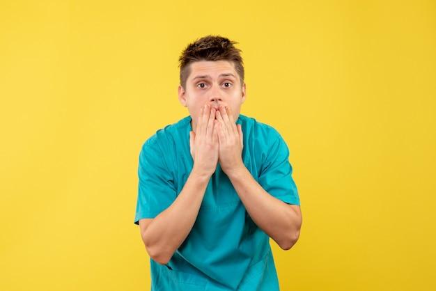 Jovem médico de frente para o terno médico surpreso com fundo amarelo