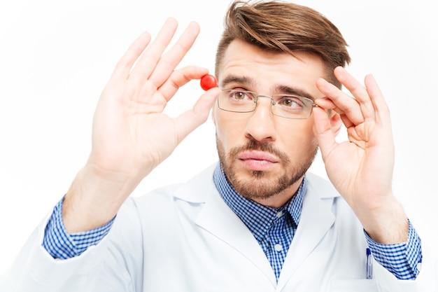 Jovem médico de óculos olhando pílula isolada em um fundo branco