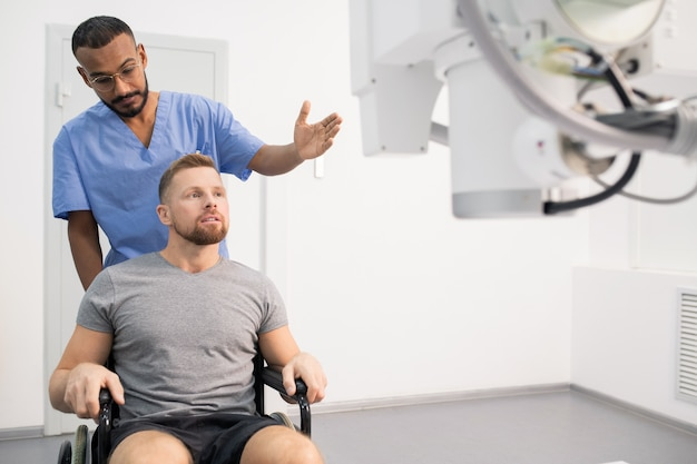 Jovem médico de uniforme mostrando um homem doente em uma cadeira de rodas novo equipamento médico enquanto aponta para ele