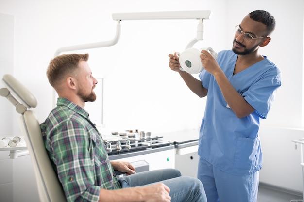 Jovem médico de uniforme segurando equipamento médico ou lâmpada enquanto fica em frente ao paciente na poltrona antes do exame