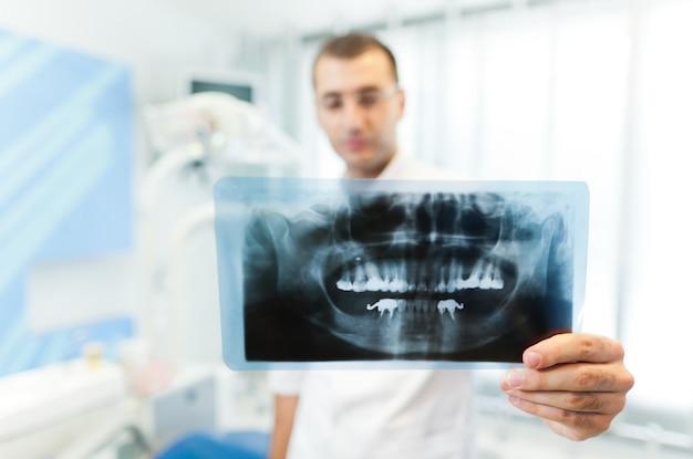 Jovem médico dentista homem de uniforme branco de pé e olhando para a foto do dente no consultório odontológico na clínica